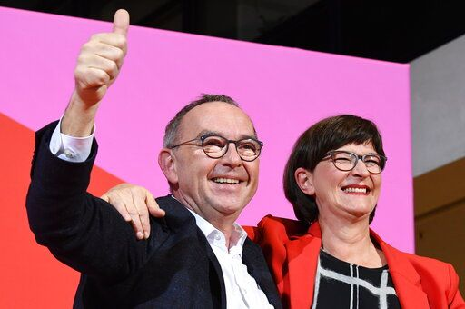Norbert Walter-Borjans, left, and Saskia Esken celebrate after winning the member voting of the Social Democratic Party, SPD, chairmanship at the party's headquarters in Berlin, Germany, Saturday, Nov. 30, 2019. Norbert Walter-Borjans and Saskia Esken beat the rival team of Vice Chancellor Olaf Scholz and Klara Geywitz in a runoff ballot of the Social Democrats' members, according to results announced Saturday. (Joerg Carstensen/dpa via AP)