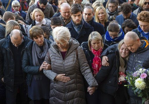 The family of Jack Merritt take part in a vigil at The Guildhall to honour him and Saskia Jones who were both killed in Friday's attack on London Bridge, in Cambridge, England, Monday, Dec. 2, 2019. London Bridge reopened to cars and pedestrians Monday, three days after a man previously convicted of terrorism offenses stabbed two people to death and injured three others before being shot dead by police. (Joe Giddens/PA via AP)