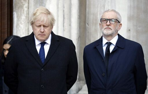 Britain's Prime Minister Boris Johnson, left, and Labour Party leader Jeremy Corbyn take part in a vigil at Guildhall Yard in London, Monday Dec. 2, 2019, to remember the London attack victims and honor members of the emergency services and bystanders who fought the attacker. London Bridge reopened to cars and pedestrians Monday, three days after a man previously convicted of terrorism offenses stabbed two people to death and injured three others before being shot dead by police.