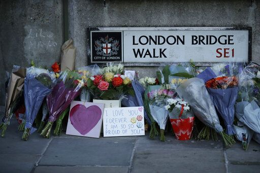 Tributes are placed by the southern end of London Bridge in London, Monday, Dec. 2, 2019. London Bridge reopened to cars and pedestrians Monday, three days after a man previously convicted of terrorism offenses stabbed two people to death and injured three others before being shot dead by police.