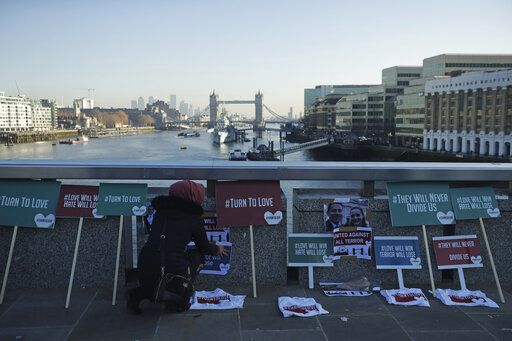A member of the Faiths Forum for London places tributes on London Bridge in London, Monday, Dec. 2, 2019. London Bridge reopened to cars and pedestrians Monday, three days after a man previously convicted of terrorism offenses stabbed two people to death and injured three others before being shot dead by police.