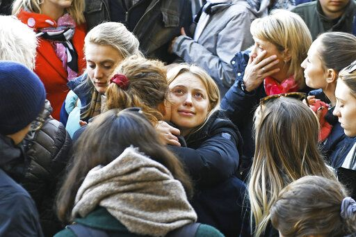 Leanne O'Brien, centre, the girlfriend of Jack Merritt, is comforted by family members during a vigil at The Guildhall to honour him and Saskia Jones who were both killed in Friday's attack on London Bridge, in Cambridge, England, Monday, Dec. 2, 2019. London Bridge reopened to cars and pedestrians Monday, three days after a man previously convicted of terrorism offenses stabbed two people to death and injured three others before being shot dead by police. (Joe Giddens/PA via AP)