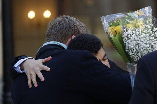 People embrace before attending a vigil at Guildhall Yard in London, Monday Dec. 2, 2019, to remember the London attack victims and honor members of the emergency services and bystanders who fought the attacker. London Bridge reopened to cars and pedestrians Monday, three days after a man previously convicted of terrorism offenses stabbed two people to death and injured three others before being shot dead by police.