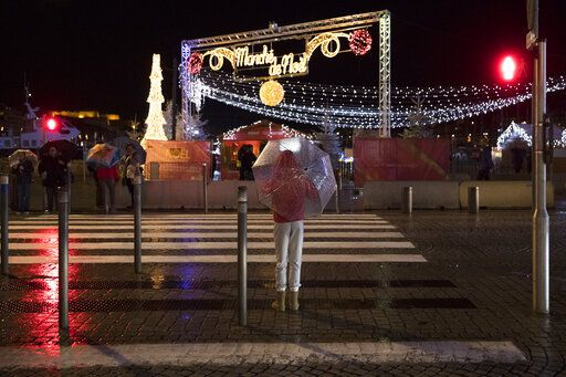 A pedestrian waits with an umbrella to cross the road during a storm in Marseille, Sunday, Dec. 1, 2019. The southern France region is under a red alert for heavy rain and floods.