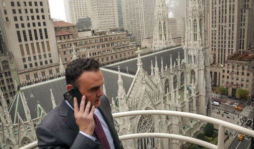In this Tuesday, Oct. 29, 2019, photo, attorney Adam Slater takes a phone call on a patio outside his high-rise Manhattan office overlooking St. Patrick's Cathedral, in New York. Slater's firm is representing clients accusing the Roman Catholic Church of sexual abuse, a clientele that is rapidly growing after New York state opened its one-year window allowing sex abuse suits with no statute of limitations.
