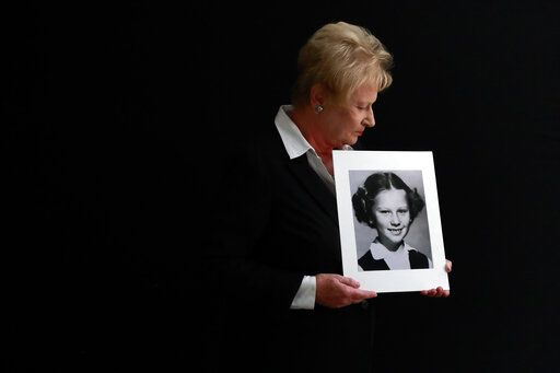 In this Nov. 20, 2019, photo, Nancy Holling-Lonnecker, 71, poses with a picture taken of her as a young girl, at her home in San Diego. Holling-Lonnecker plans to take advantage of an upcoming three-year window in California that allows people to make claims of sexual abuse no matter how old. Her claim dates back to the 1950s when she says a priest repeatedly raped her in a confession booth beginning when she was 7 years old. 'œThe survivors coming forward now have been holding on to this horrific experience all of their lives,'� she said.