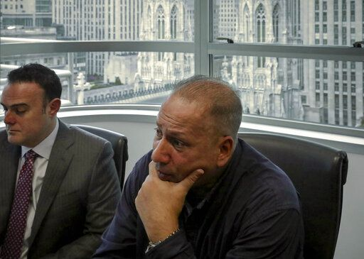 In this Tuesday, Oct. 29, 2019, photo, Ramon Mercado, right, recalls childhood clergy sexual abuse while his lawyer, Adam Slater, left, takes notes during an interview in his office overlooking St. Patrick's Cathedral, in New York. Mercado said he kept silent about the abuse he suffered at the hands of a New York priest, in part not to upset his devout Catholic mother.