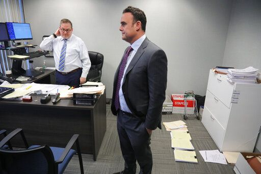 In this Tuesday, Oct. 29, 2019, photo, attorney Adam Slater, right, meets with his firm's managing attorney, Steven Alter, left, in Melville, N.Y. Slater said since New York state opened its one-year window allowing sex abuse suits with no statute of limitations, his firm has signed up nearly 300 new clients, prompting new hires of paralegals to field calls.