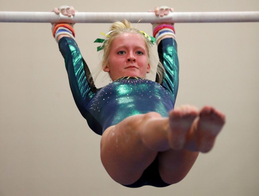 Elk Grove's Hannah Baumeister competes on the parallel bars during varsity girls gymnastics at Barrington Monday.