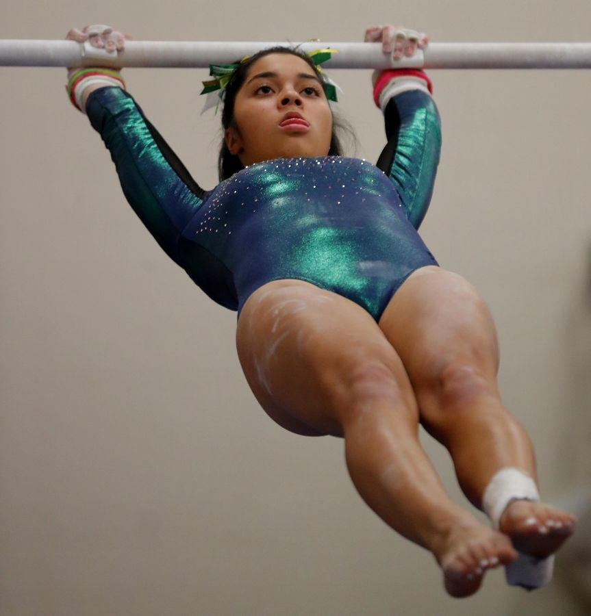 Elk Grove's Katie Talens competes on the parallel bars during varsity girls gymnastics at Barrington Monday.