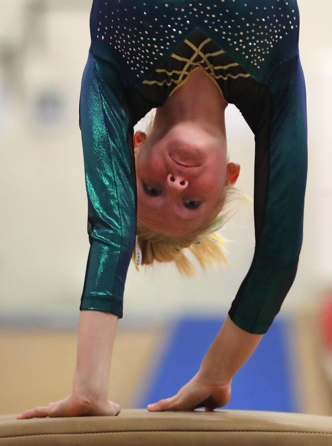 Elk Grove's Hannah Baumeister competes on the vault during varsity girls gymnastics at Barrington Monday.