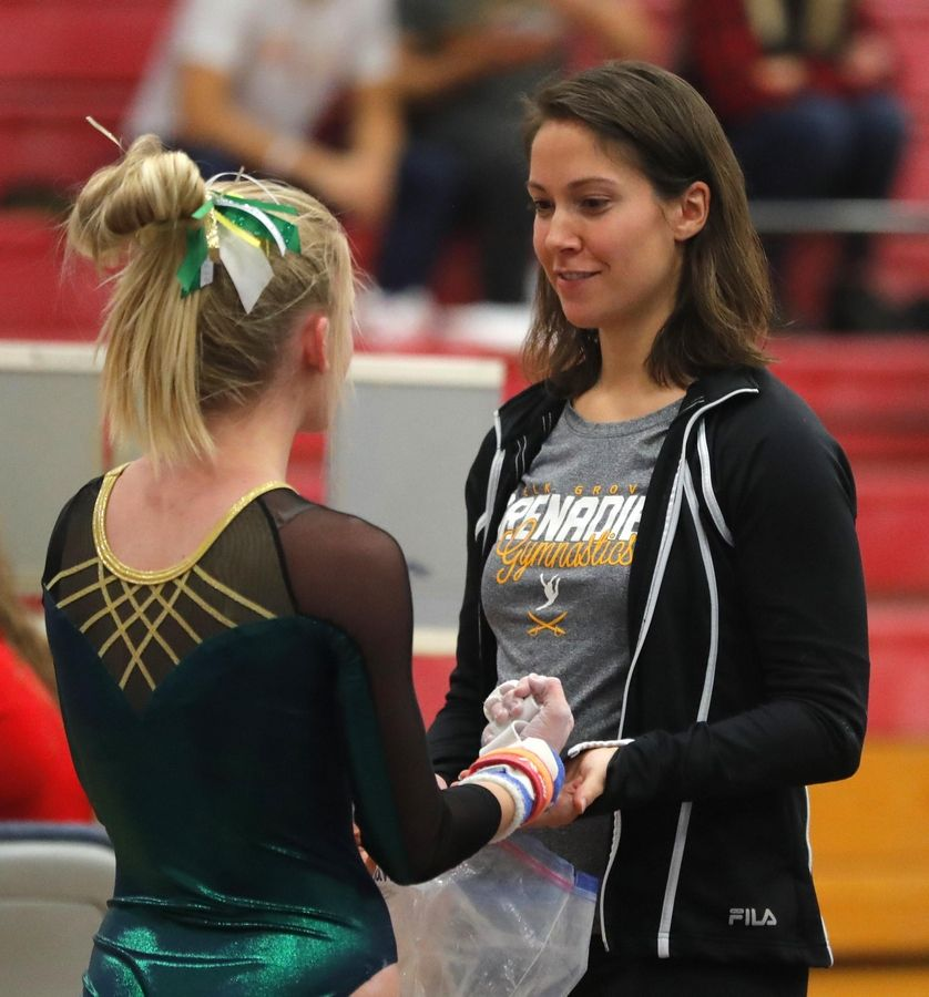 Elk Grove head coach Amy Rivera encourages Hannah Baumeister after a parallel bars routine during varsity girls gymnastics at Barrington Monday.