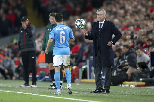 Napoli's head coach Carlo Ancelotti throws the ball to Napoli's Mario Rui, 6, during the Champions League Group E soccer match between Liverpool and Napoli at Anfield stadium in Liverpool, England, Wednesday, Nov. 27, 2019.