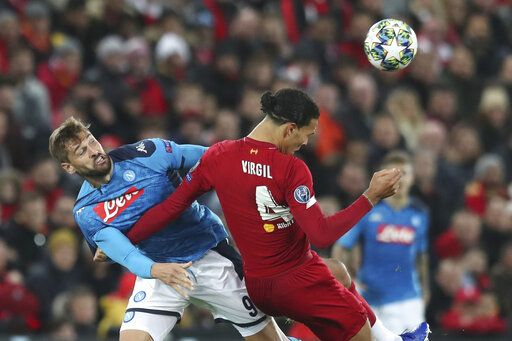 Napoli's Fernando Llorente, left, competes for the ball with Liverpool's Virgil van Dijk during the Champions League Group E soccer match between Liverpool and Napoli at Anfield stadium in Liverpool, England, Wednesday, Nov. 27, 2019.