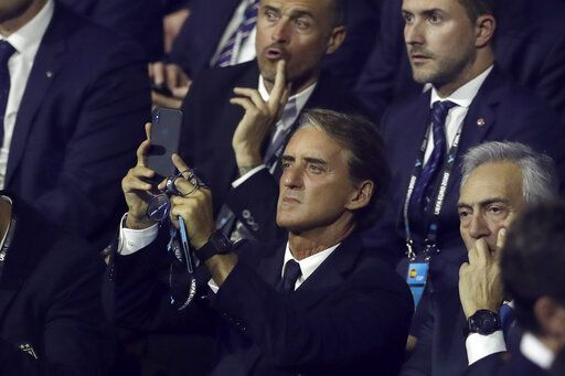Italy coach Roberto Mancini takes pictures while waiting for the start of the draw for the UEFA Euro 2020 soccer tournament finals in Bucharest, Romania, Saturday, Nov. 30, 2019.