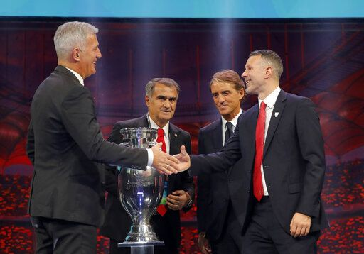 The coaches of Switzerland Vladimir Petkovic, left, Turkey Senol Gunes, second left, Italy Roberto Mancini, second right, and Wales Ryan Giggs who will play in group A, pose with the trophy after the draw for the UEFA Euro 2020 soccer tournament finals in Bucharest, Romania, Saturday, Nov. 30, 2019.