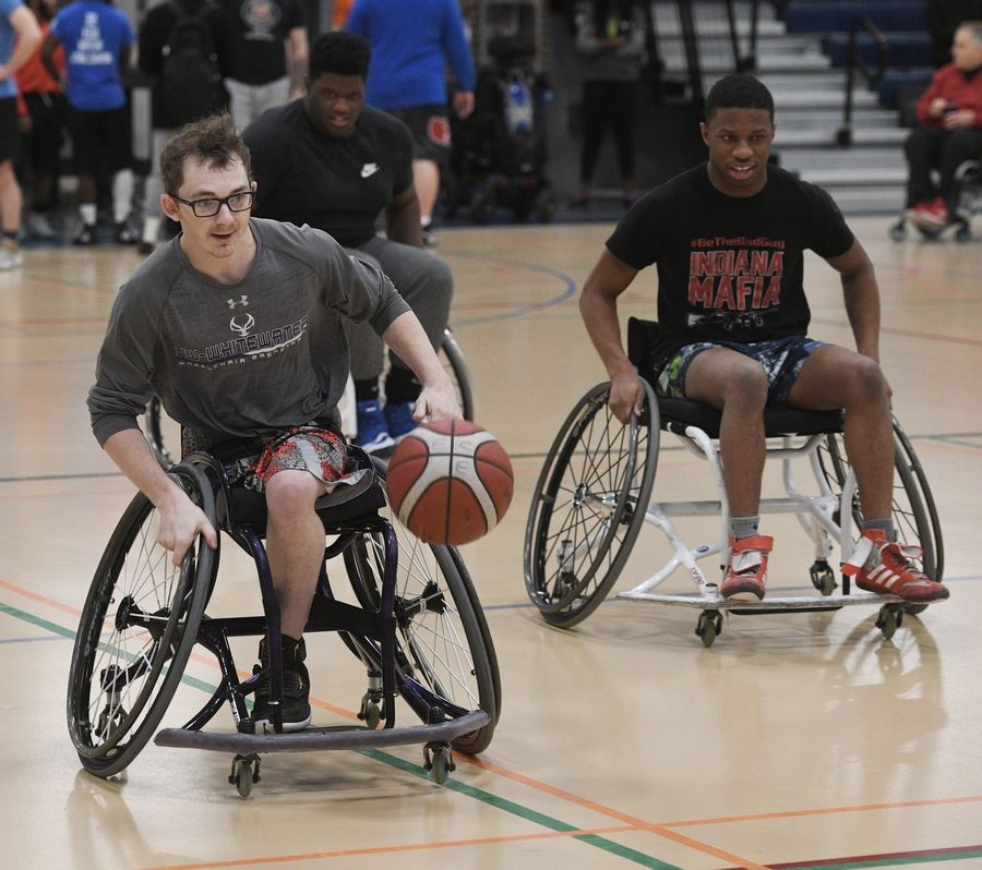 University of Wisconsin-Whitewater player Dylan Fischbach leads a fast break, with Harper College student Terrell Leavell of Indianapolis, Indiana, pursuing, during a wheelchair basketball demonstration at the inaugural Harper College Adaptive Sports Day in Palatine Tuesday.