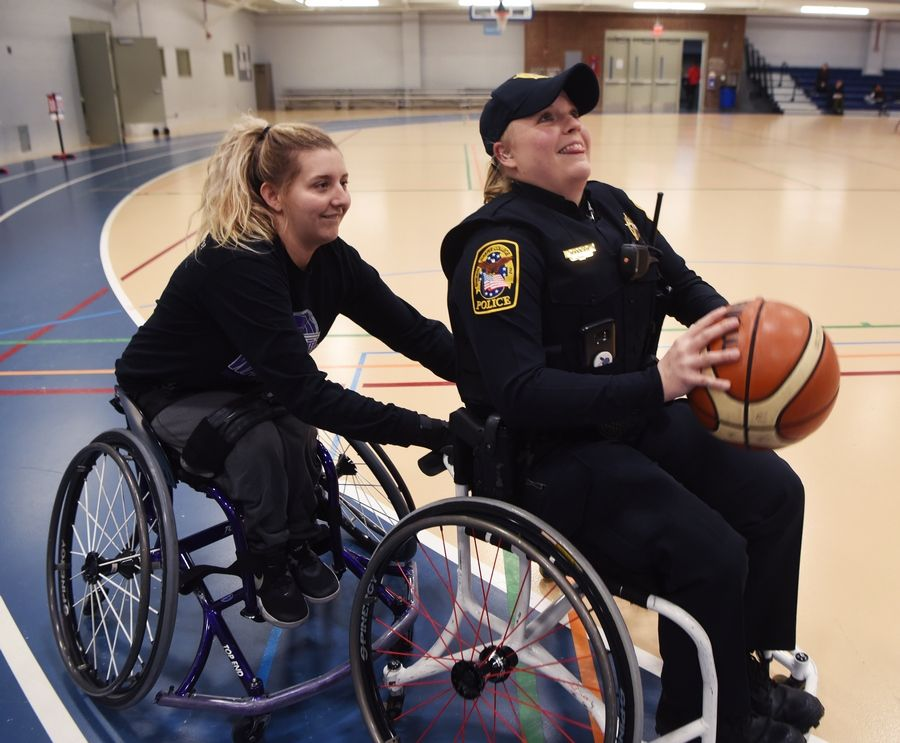 Harper College police officer Melissa Harrah gets an extra boost of forward momentum from University of Wisconsin-Whitewater player Josie DeHart during a wheelchair basketball demonstration Tuesday at the inaugural Harper College Adaptive Sports Day in Palatine.