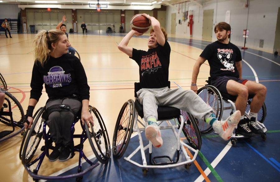 Alex Petro, a Harper College student from Rolling Meadows and a member of the wrestling team, shoots while flanked by wrestling teammate John Wright, also of Rolling Meadows, right, and Josie DeHart, a member of the University of Wisconsin Whitewater women's wheelchair basketball team, during a wheelchair basketball demonstration Tuesday at the inaugural Harper College Adaptive Sports Day in Palatine.