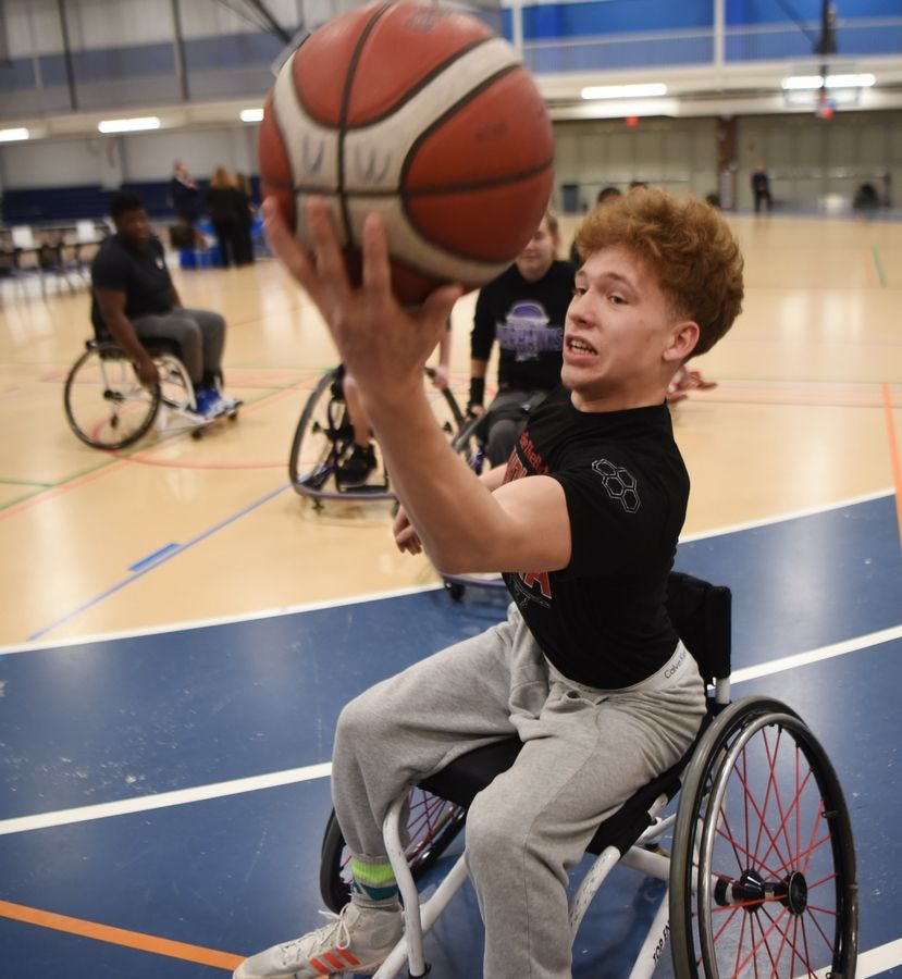 Alex Petro, a Harper College student from Rolling Meadows and a member of the wrestling team, keeps the ball from going out of bounds during a wheelchair basketball demonstration by the University of Wisconsin-Whitewater men's and women's teams at the inaugural Harper College Adaptive Sports Day in Palatine Tuesday.