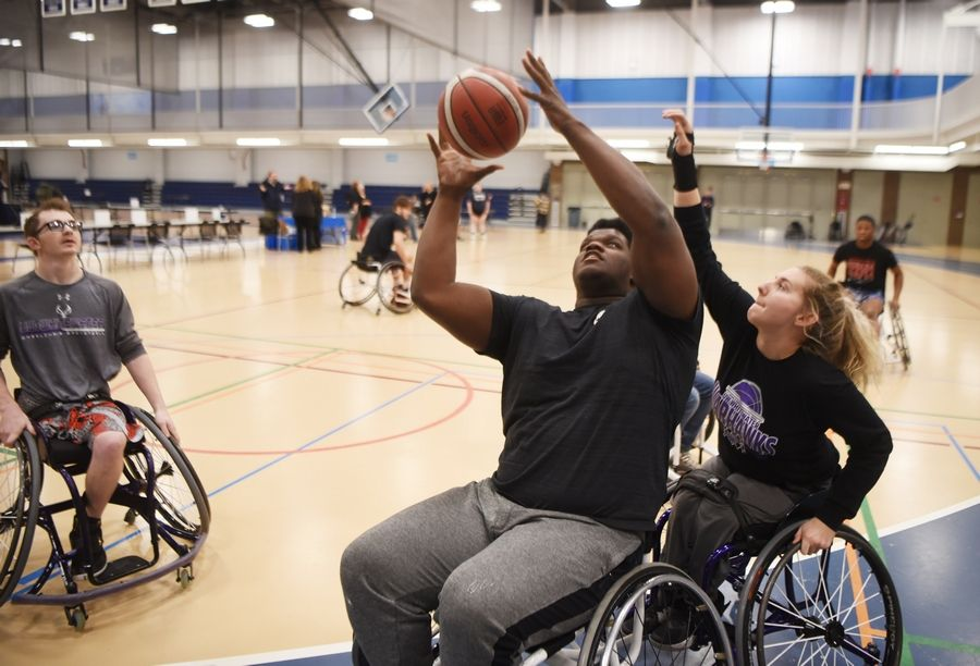 Harper College student and wrestler Johnathan Cooper of Wheaton attempts a shot while being guarded by Josie DeHart of the during a wheelchair basketball demonstration Tuesday at the inaugural Harper College Adaptive Sports Day in Palatine.