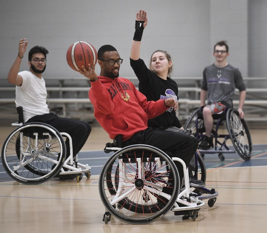 Harper College student Jeremiah Blocker of Hoffman Estates looks for an open teammate while being guarded by University of Wisconsin-Whitewater player Josie DeHart during a wheelchair basketball demonstration Tuesday at the inaugural Harper College Adaptive Sports Day in Palatine.