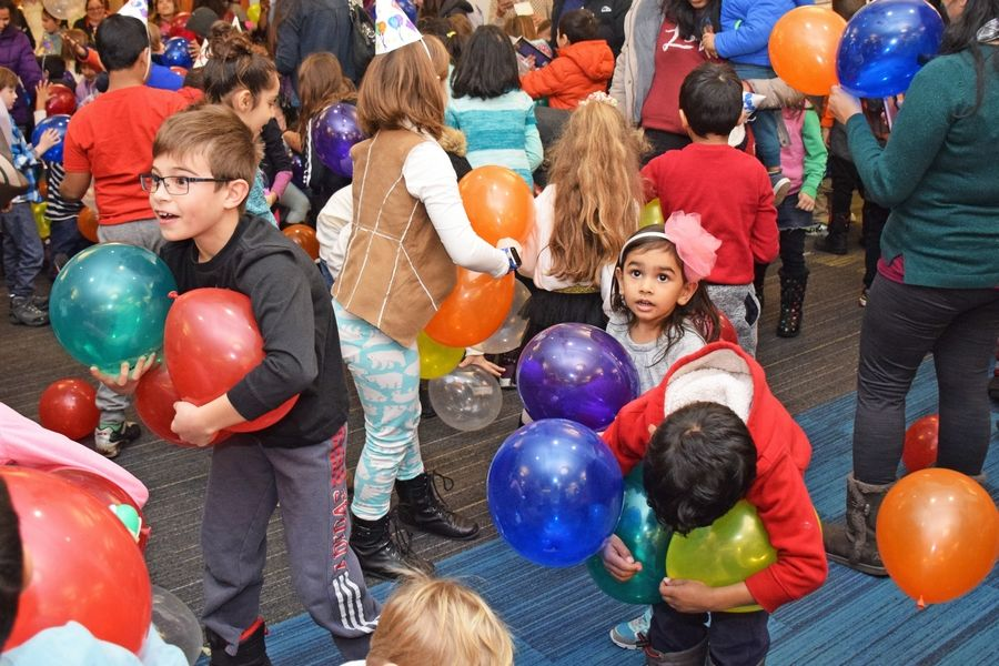 Children catch balloons during a previous Noon Year's Eve celebration at the Schaumburg Township District Library. See article for details on the upcoming Noon Year's Eve event.  Susan Miura