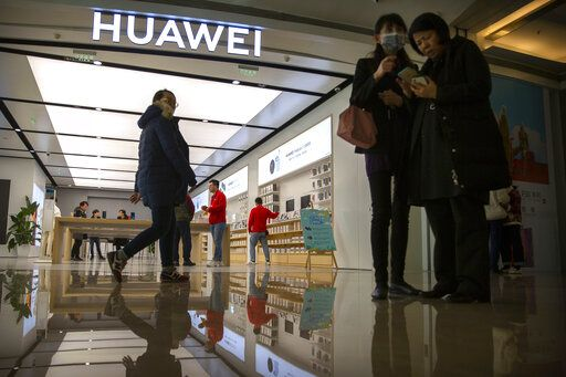 In this Nov. 20, 2019, photo, people stand outside of a Huawei store at a shopping mall in Beijing. The founder of Huawei says the Chinese tech giant is moving its U.S. research center to Canada due to American restrictions on its activities.
