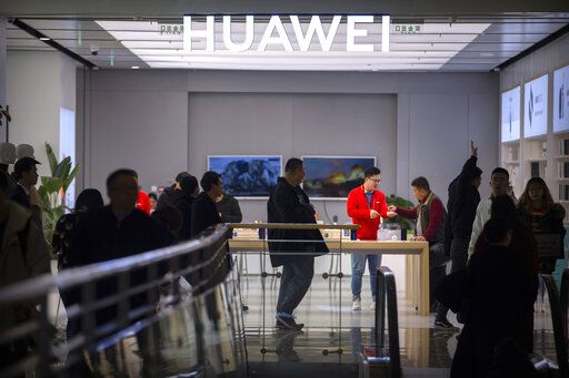 In this Nov. 20, 2019, photo, customers shop at a Huawei store at a shopping mall in Beijing. The founder of Huawei says the Chinese tech giant is moving its U.S. research center to Canada due to American restrictions on its activities.