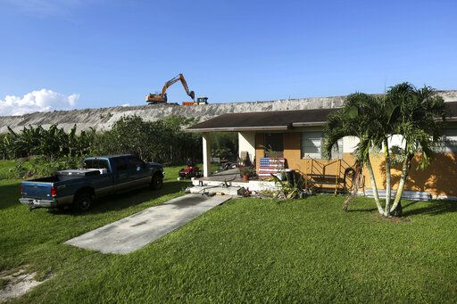 In this Friday, Nov. 1, 2019 photo, rehabilitation work takes place on top of the Herbert Hoover Dike surrounding Lake Okeechobee, just a few feet from a home in Pahokee, Fla. Hurricane tides overtopped the original dike in 1926 and 1928, washed away houses and caused over 2,500 deaths.