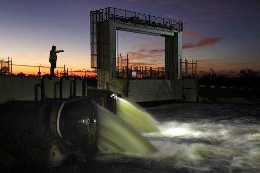 In this Monday, Oct. 28, 2019 photo, water is discharged from a flood control station along the Tamiami Trail in Miami, Fla., into a canal that drains into Everglades National Park. Heavy rains that often flood a conservation area north of the station trigger flushing of the canal, raising environmental worries about the quality of water flowing into the park.