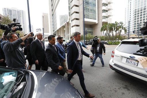 California Republican Rep. Duncan Hunter, center right, walks out of federal court Tuesday, Dec. 3, 2019, in San Diego. Hunter gave up his year-long fight against federal corruption charges and pleaded guilty Tuesday to misusing his campaign funds, paving the way for the six-term Republican to step down.