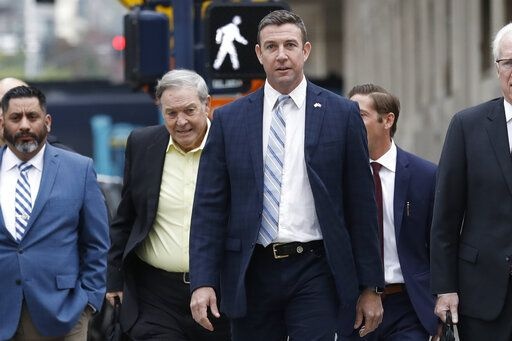 California Republican Rep. Duncan Hunter, center, walks towards federal court in front of his father, former Rep. Duncan L. Hunter, left, Tuesday, Dec. 3, 2019, in San Diego. Hunter said in a TV interview that aired Monday he plans to plead guilty to the misuse of campaign funds at a federal court hearing Tuesday in San Diego.