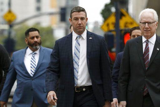 California Republican Rep. Duncan Hunter, center, walks towards federal court Tuesday, Dec. 3, 2019, in San Diego. Hunter said in a TV interview that aired Monday he plans to plead guilty to the misuse of campaign funds at a federal court hearing Tuesday in San Diego.