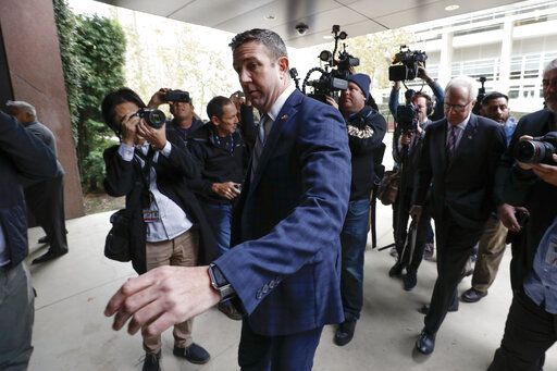 California Republican Rep. Duncan Hunter reaches to open the door to federal court Tuesday, Dec. 3, 2019, in San Diego. Hunter said in a TV interview that aired Monday he plans to plead guilty to the misuse of campaign funds at a federal court hearing Tuesday in San Diego.