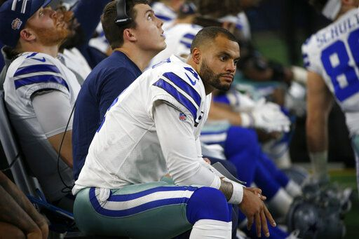 Dallas Cowboys quarterback Dak Prescott (4) and offensive coordinator Kellen Moore, rear, sit on the bench late in the second half of an NFL football game against the Buffalo Bills in Arlington, Texas, Thursday, Nov. 28, 2019.