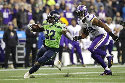 Seattle Seahawks' Chris Carson runs on a 26-yard carry as Minnesota Vikings' Danielle Hunter pursues during the second half of an NFL football game, Monday, Dec. 2, 2019, in Seattle.