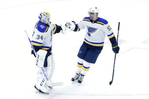 St. Louis Blues goaltender Jake Allen, left, and David Perron celebrate their win over the Chicago Blackhawks in an NHL hockey game Monday, Dec. 2, 2019, in Chicago.