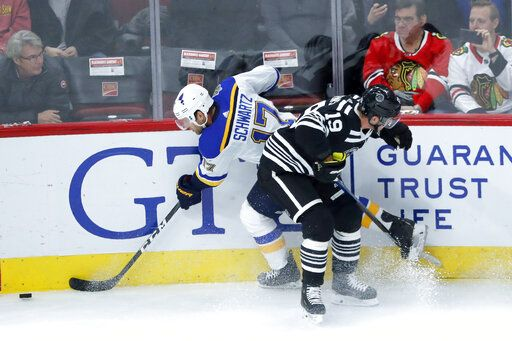 Chicago Blackhawks' Jonathan Toews (19) checks St. Louis Blues' Jaden Schwartz against the boards during the first period of an NHL hockey game Monday, Dec. 2, 2019, in Chicago.