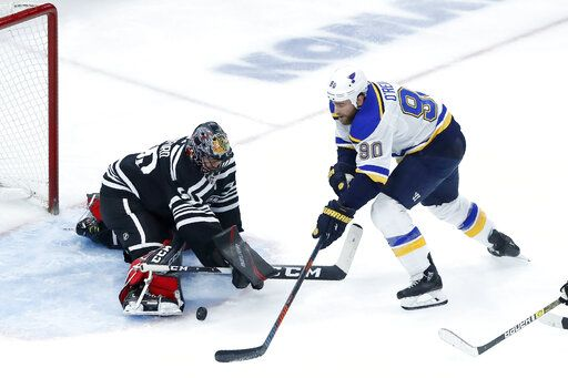 Chicago Blackhawks goaltender Corey Crawford, left, makes a save on a shot by St. Louis Blues' Ryan O'Reilly during the second period of an NHL hockey game Monday, Dec. 2, 2019, in Chicago.