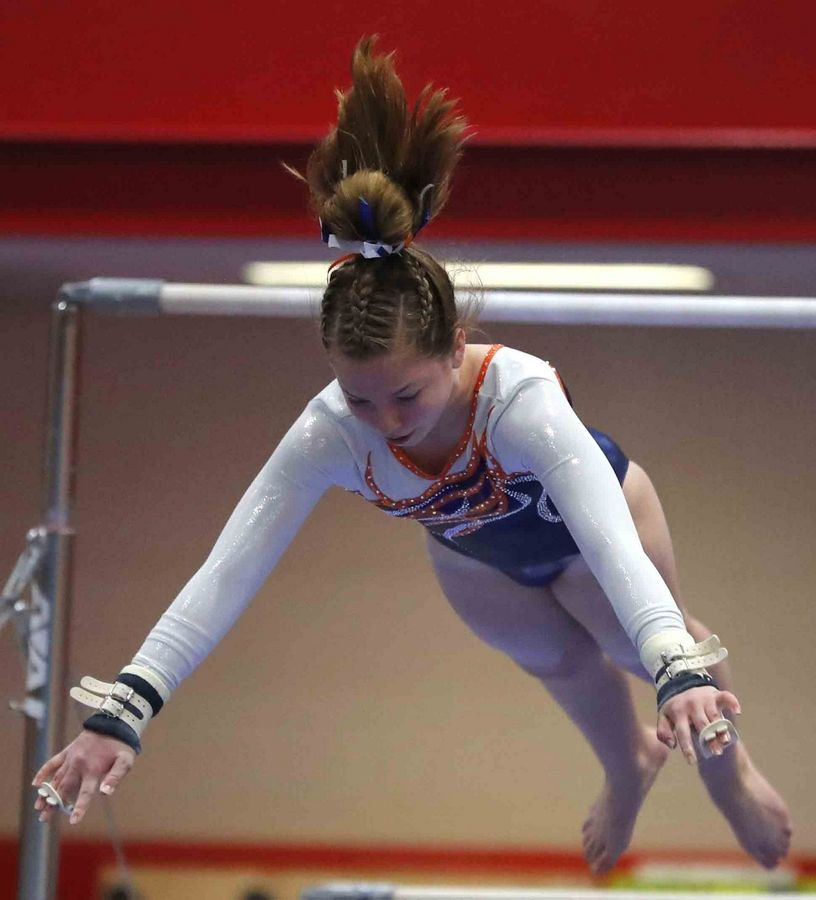 Buffalo Grove's Anna Lang performs on the bars in varsity girls gymnastics at Palatine High School Wednesday.
