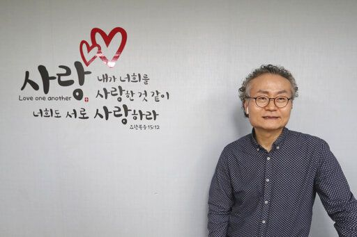 "In this Nov. 1, 2019, photo, Shim Yang-sup, the principal of the Seoul-based alternative South-North Love School, speaks during an interview at his school in Seoul, South Korea. Hundreds of children born to North Korean women and Chinese men have resettled in South Korea, but life is often tough. The sign reads ""Love one another as I love you.""  Shim said the children should be supported because they represent an untapped resource, with the ability to often speak two languages and navigate both Korean and Chinese cultures."