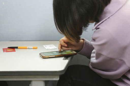 In this Nov. 1, 2019, photo, 20 years old student Choe watches her smartphone before an interview at the South-North Love School in Seoul, South Korea. Choe is half-Chinese, half-North Korean young woman - who wished to be identified only by her family name, Choe, because she worries that media publicity could damage her life in South Korea - came to Seoul from China last year to reunite with her North Korean refugee mother.