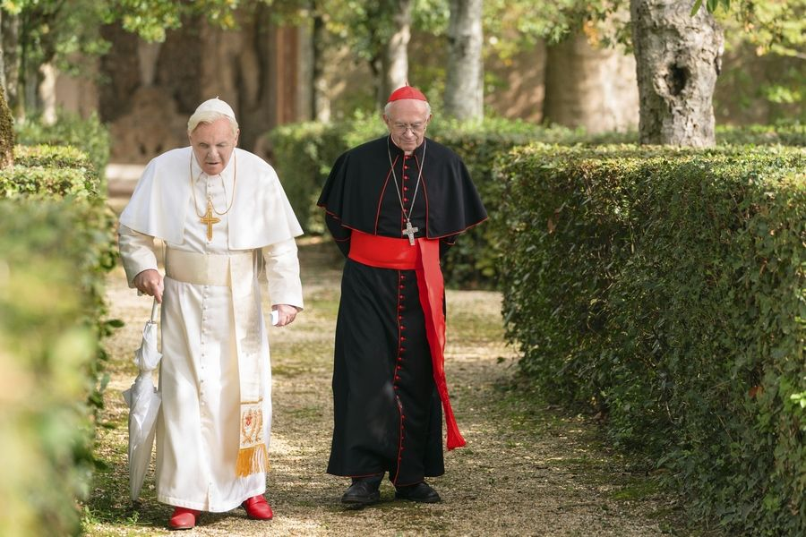 "Cardinal Bergoglio (Jonathan Pryce) verbally jousts with Pope Benedict (Anthony Hopkins) in ""The Two Popes."""