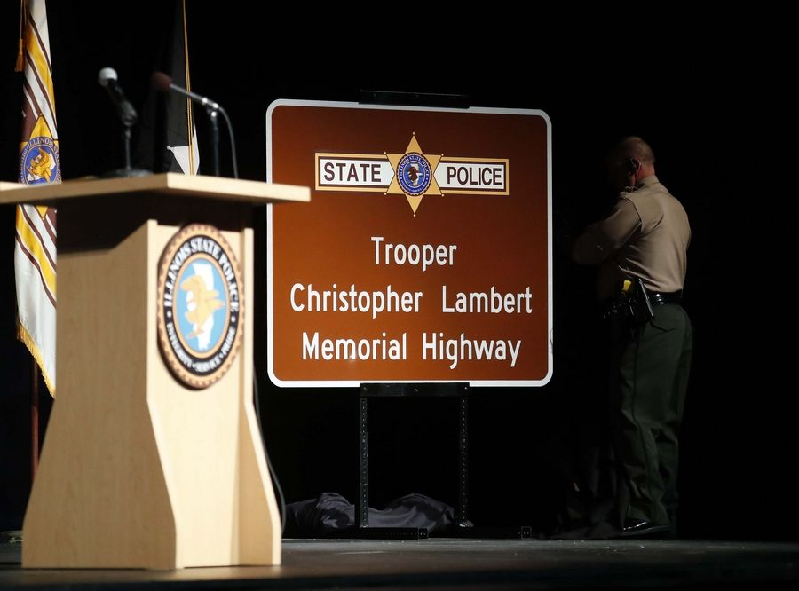 "A sign designating a section of I-294 near Willow Road as the ""Trooper Christopher Lambert Highway"" was unveiled Thursday during a dedication ceremony in Rosemont. Lambert, 34, of Highland Park, was killed in the line of duty Jan. 12."