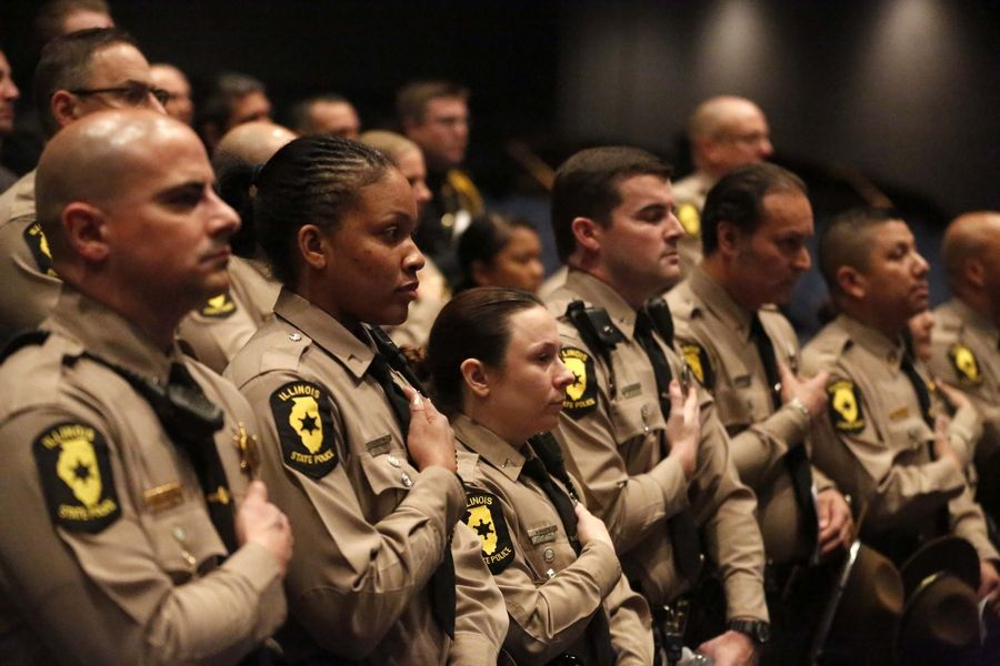 Illinois State Police troopers cover their hearts during the singing of the national anthem as they joined elected officials, friends, colleagues and family members paying tribute Thursday to fallen Trooper Christopher Lambert.