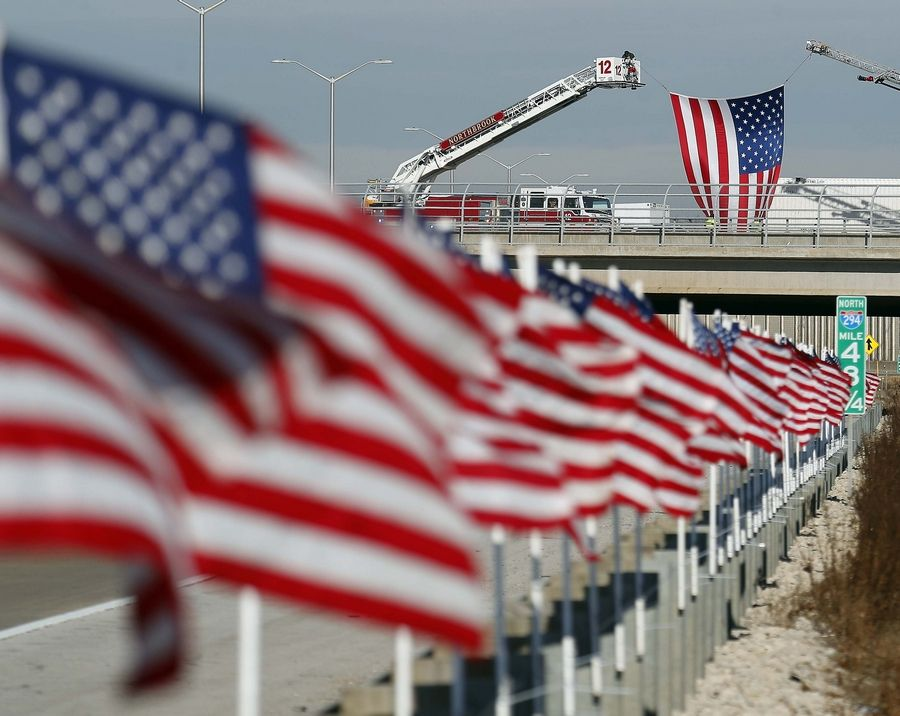 "American flags adorn a stretch of I-294 designated Thursday as the ""Trooper Christopher Lambert Highway"" in honor of a fallen state trooper from Highland Park."