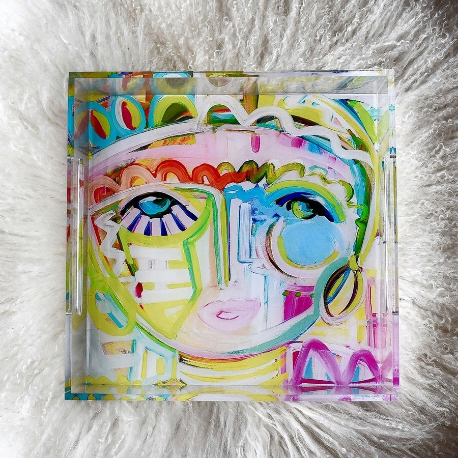 "Artist Windy O'Connor shows one of her ""Tropicana Chica"" acrylic trays. O'Connor likes giving small home accessories like this tray as holiday gifts because the recipient can use them in so many different ways, from decorating a coffee table to serving cookies or desserts at a party."
