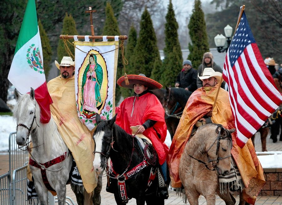 Riders carrying flags of Mexico, Our Lady of Guadalupe and the United States lead a procession of about 200 horses carrying members of Club Los Vaqueros Unidos from the Chicago area on the way to place roses at the Shrine of Our Lady of Guadalupe in Des Plaines on Dec. 1, 2018, ahead of the feast day. They'll do the same Saturday.