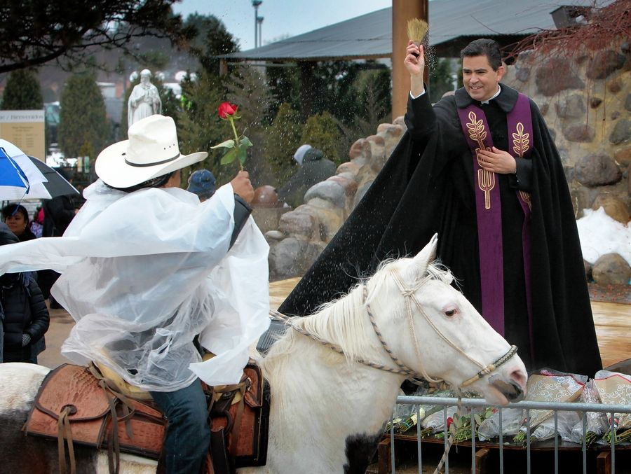 The Very Rev. Esequiel Sanchez, rector of Shrine of Our Lady of Guadalupe in Des Plaines, blesses horse riders as they pass by in 2018. Following a Saturday morning Mass in a forest preserve near Wheeling, about 100 horseback riders from Club Los Vaqueros Unidos will start a procession to the shrine as the unofficial local start of the Feast of Our Lady of Guadalupe that Catholics around the world will celebrate Thursday.